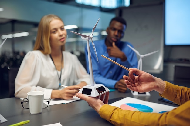 Equipe de jovens gerentes com modelos de moinhos de vento, conferência no escritório de ti. trabalho em equipe e planejamento profissional, brainstorming de grupo e trabalho corporativo, reunião de colegas