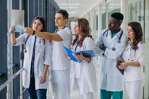 Equipe de jovens médicos especialistas em pé no corredor do hospital
