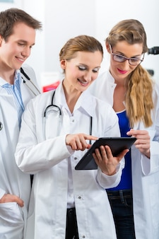 Equipe de jovens médicos na clínica com computador tablet