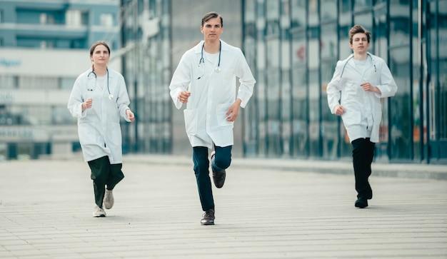 Equipe de jovens profissionais médicos correndo rapidamente para ajudar