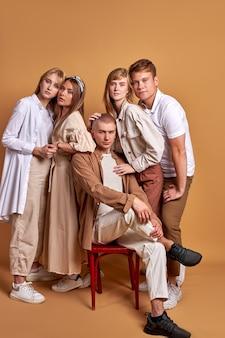 Equipe de jovens unidos posando com roupas da moda em tons pastel, lindos homens e mulheres reunidos