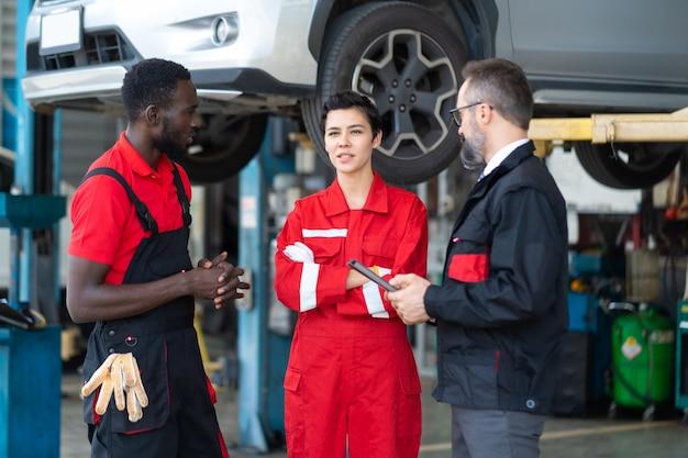 Equipe de mecânicos discutindo na oficina mecânica. equipe de mecânica profissional especializada em oficina mecânica.