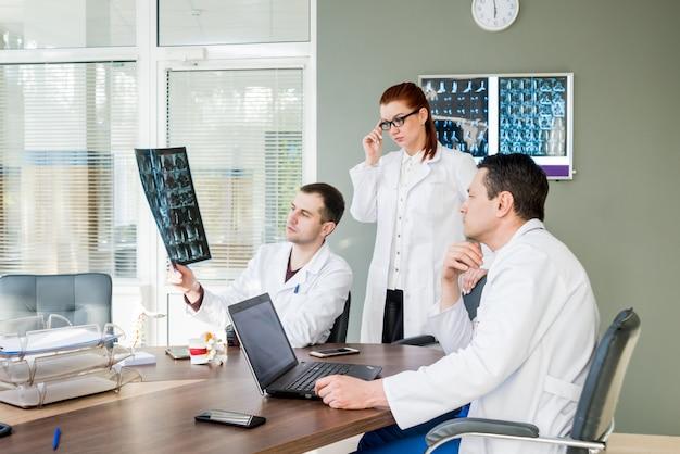 Equipe de médicos com conselho médico no hospital. discutindo questões médicas. sistemas de fixação da coluna