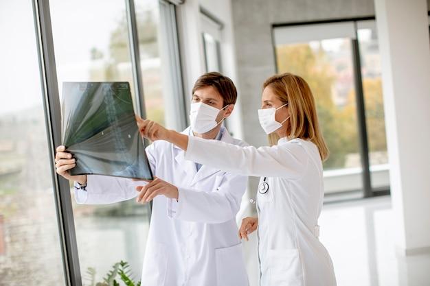 Equipe de médicos com máscaras faciais de proteção examinando radiografia no consultório