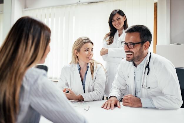 Equipe de médicos contando boas notícias para uma paciente do sexo feminino.