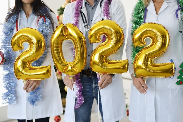 Equipe de médicos de jaleco branco segurando números conceito de ano novo e natal