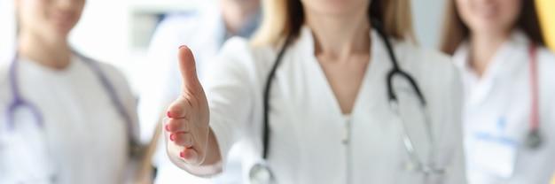 Equipe de médicos de jaleco branco sorrindo e estendendo as mãos em um gesto amigável
