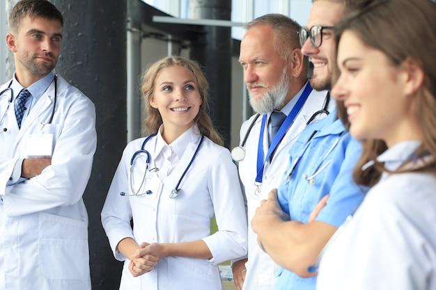 Equipe de médicos diferentes conversando no hospital.