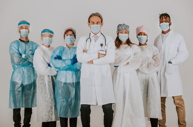 Equipe de médicos e enfermeiras vestindo roupas de proteção descartáveis e máscaras faciais para lutar contra covid19