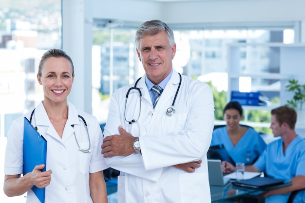 Equipe de médicos em pé de braços cruzados e sorrindo para a câmera