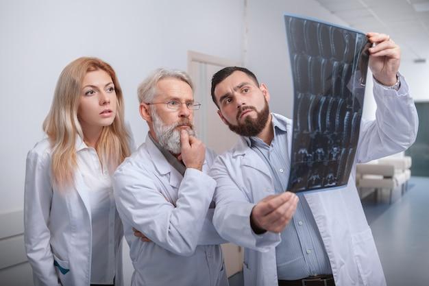 Equipe de médicos examinando ressonância magnética juntos