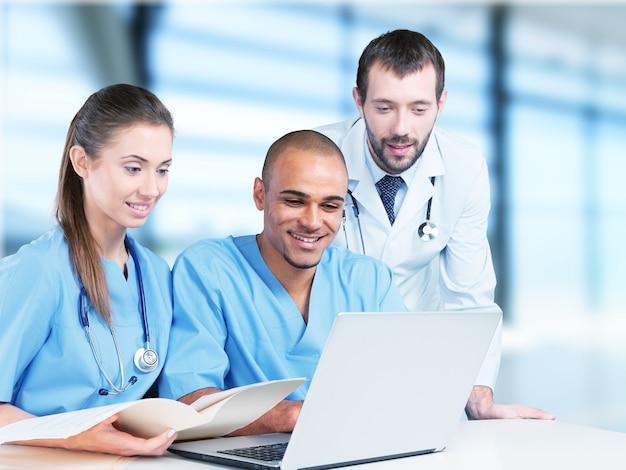 Equipe de médicos falando sobre experiência em hospital por laptop