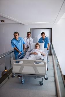Equipe de médicos, levando a mulher grávida para o teatro de operação