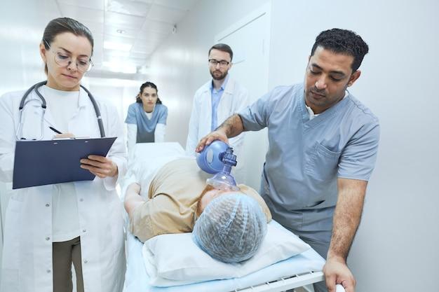 Equipe de médicos salvando paciente na cama fazendo reanimação com desfibrilador em emergência