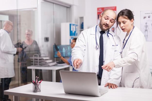 Equipe de médicos trabalhando juntos no escritório do hospital, olhando para o laptop, verificando o relatório do paciente. médico sênior com velho doente no corredor da clínica e enfermeira está segurando uma imagem de raio-x.