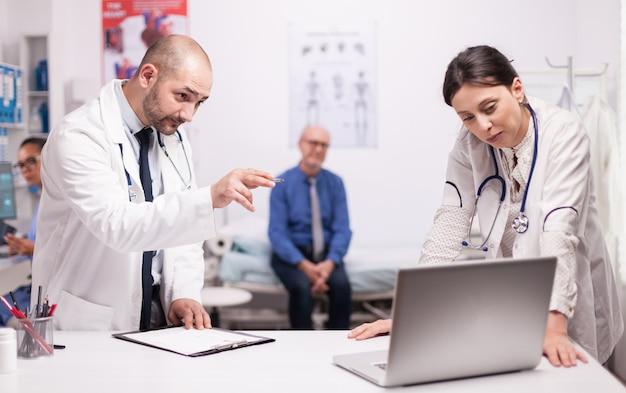 Equipe de médicos verificando o diagnóstico do paciente no laptop enquanto ele está sentado preocupado na cama do hospital. último homem durante a consulta. médicos com estetoscópio.