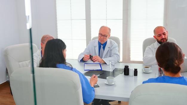 Equipe de médicos verificando relatórios de pacientes, analisando lista de espera e desenvolvimento de tratamento, enfermeira fazendo anotações. terapeuta especialista em clínica falando com colegas sobre doenças, profissional de medicina