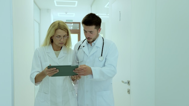 Equipe de médicos, vestindo jaleco, discutindo o exame médico do paciente, caminhando no corredor do hospital. diversos médicos estudando diagnóstico na área de transferência no corredor da clínica.