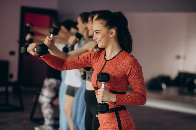 Equipe de meninas exercitando aeróbica juntos no ginásio
