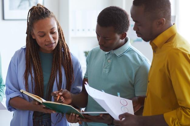 Equipe de negócios afro-americana ouvindo uma líder feminina dando instruções durante uma reunião no escritório