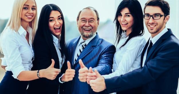Equipe de negócios amigável de sucesso no fundo do escritório, todos mostrando os polegares para cima