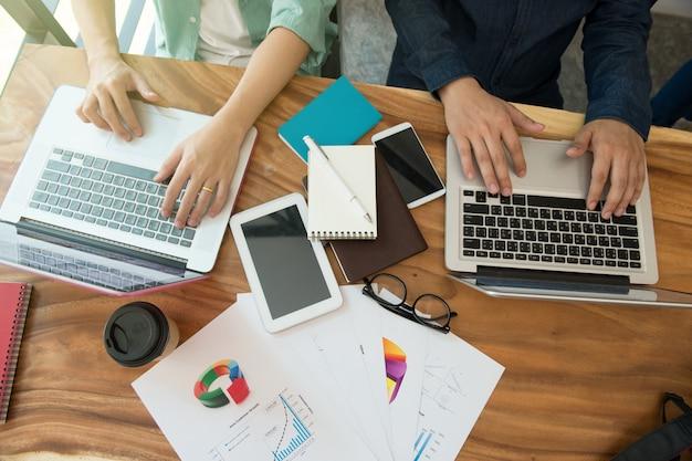 Equipe de negócios, analisando a estratégia de marketing com telefone inteligente, tablet, notebook e laptop.