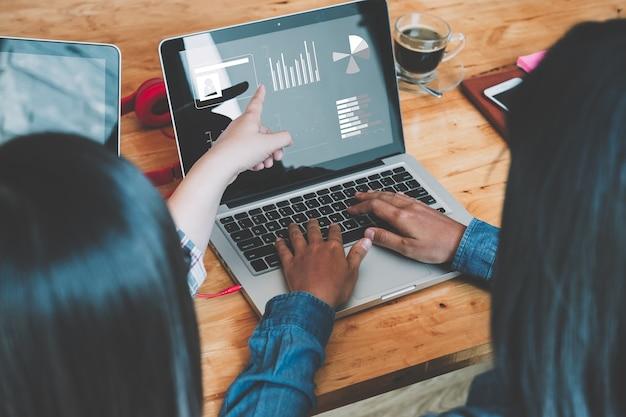 Equipe de negócios, analisando gráficos e diagramas de renda com laptop moderno