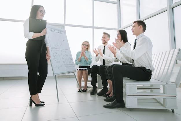 Equipe de negócios aplaude o palestrante na apresentação do novo projeto. conceito de sucesso