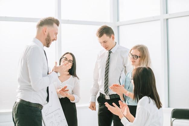 Equipe de negócios aplaudindo após uma apresentação de negócios de sucesso.