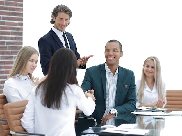 Equipe de negócios aplaudindo parceiros de negócios após a assinatura do contrato. o conceito de cooperação