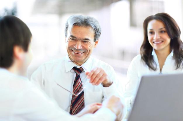 Equipe de negócios bem-sucedida de três pessoas sentadas no escritório e planejando o trabalho