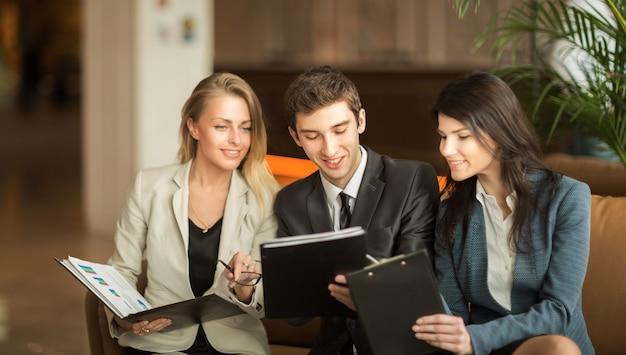Equipe de negócios bem-sucedida discutindo documentos financeiros, sentada no sofá no saguão de um escritório moderno