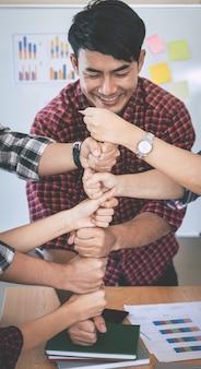 Equipe de negócios casuais está colocando o punho juntos para o conceito de equipe