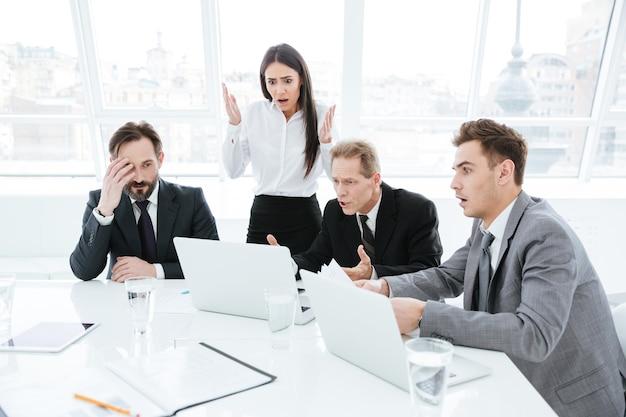 Equipe de negócios chocada perto da mesa olhando para o laptop na sala de conferências