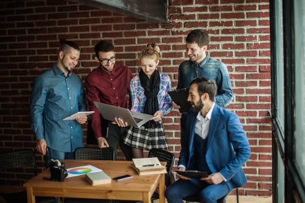 Equipe de negócios com laptop e documentos discutindo um novo projeto