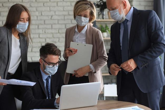 Equipe de negócios com máscaras protetoras trabalha no escritório.