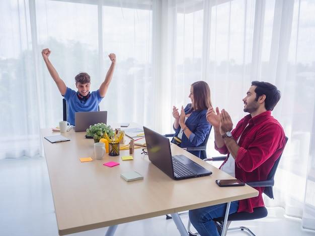 Equipe de negócios comemorando a vitória no escritório, sucesso nos negócios