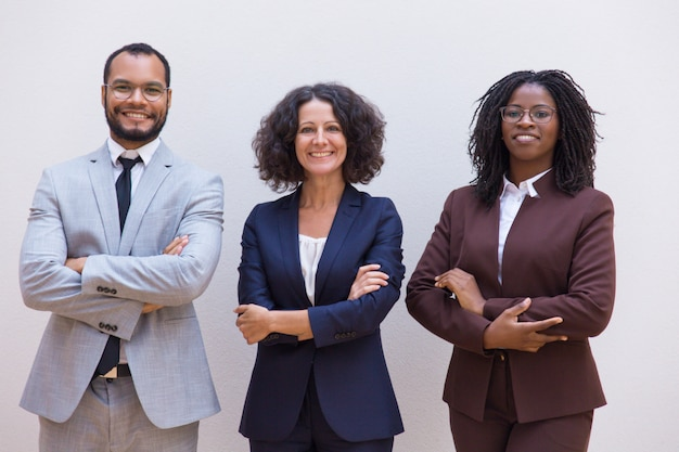Equipe de negócios confiante feliz posando com os braços cruzados