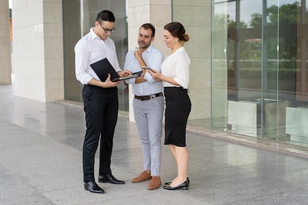 Equipe de negócios confiante lendo e discutindo documentos ao ar livre