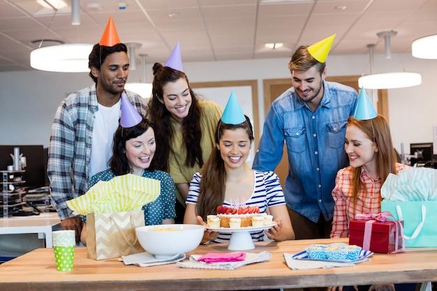 Equipe de negócios criativos comemorando aniversário de colegas no escritório