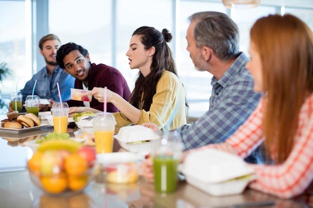 Equipe de negócios criativos fazendo refeição no escritório