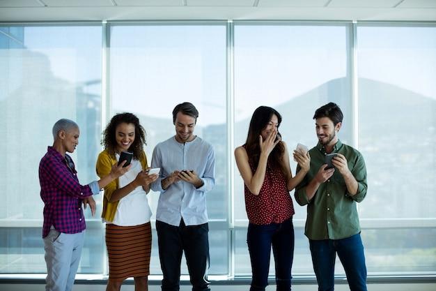 Equipe de negócios criativos interagindo ao usar o telefone celular no escritório