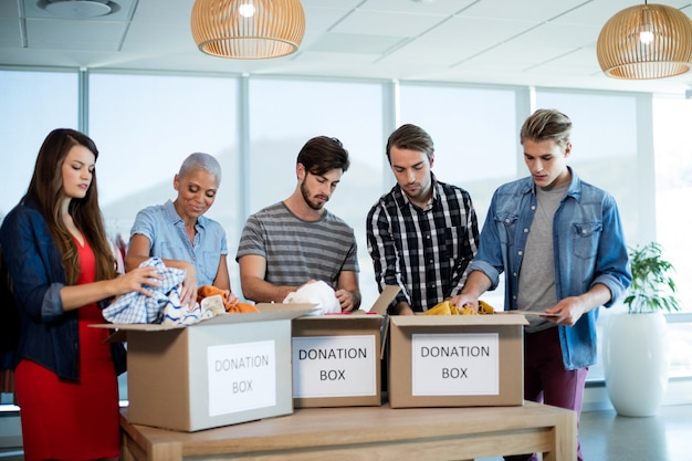 Equipe de negócios criativos separando roupas na caixa de doações no escritório