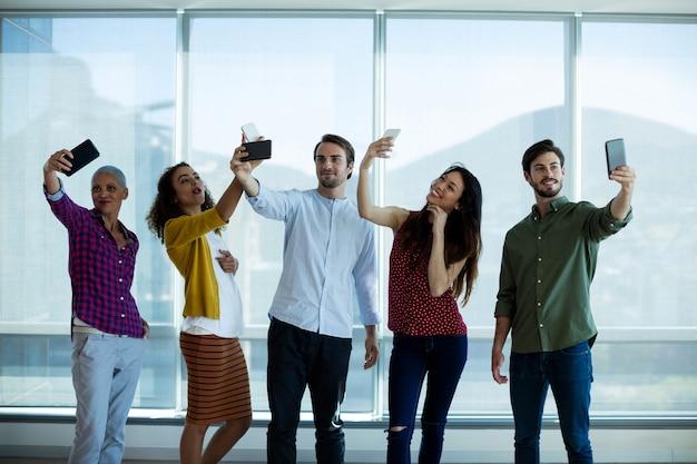Equipe de negócios criativos tirando selfie com o celular no escritório