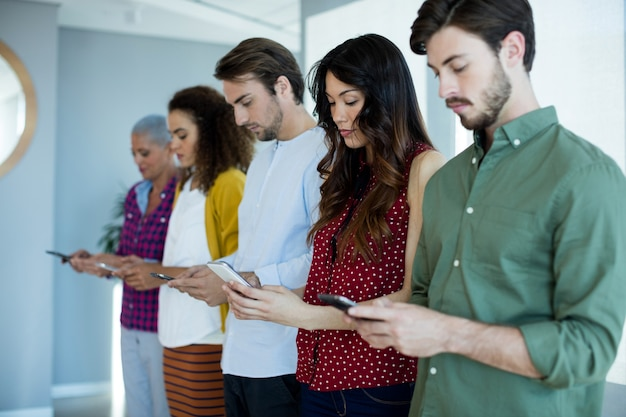 Equipe de negócios criativos usando telefone celular no escritório