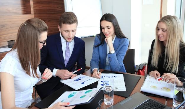 Equipe de negócios de inicialização em reunião em um moderno escritório brilhante interior de brainstorming, trabalhando em um laptop e tablet.