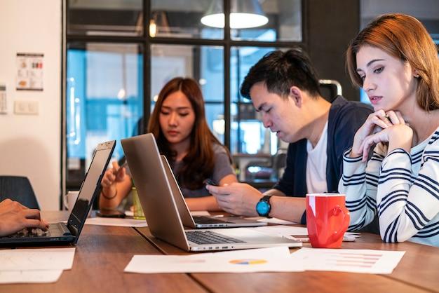 Equipe de negócios de inicialização jovem asiática em uniforme casual, discutindo e trabalhando juntos no moderno escritório de espaço de co-working.