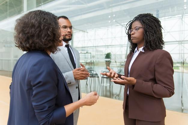 Equipe de negócios de raça mista, discutindo o projeto fora