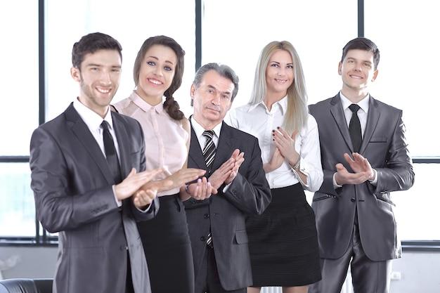 Equipe de negócios de sucesso aplaudindo no escritório. conceito de sucesso