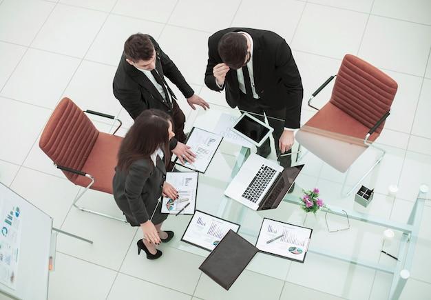 Equipe de negócios de sucesso trabalhando com gráficos financeiros e discute o lucro da empresa